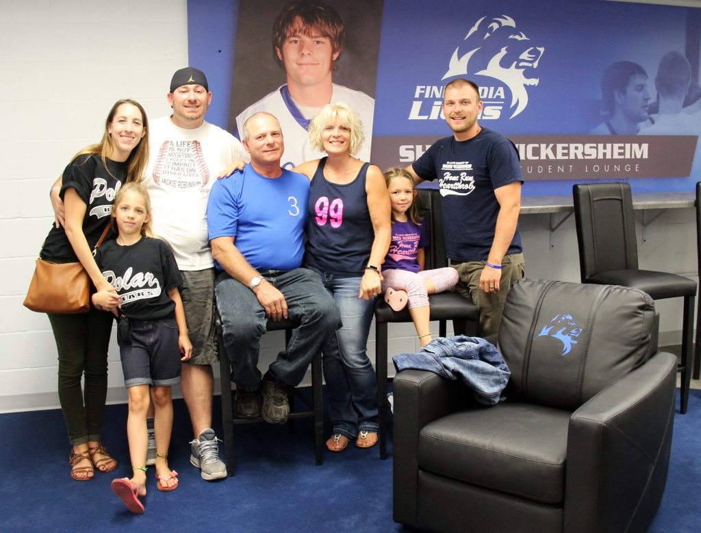 Shawn's family gathers for a photo in front of the signage in the student lounge.